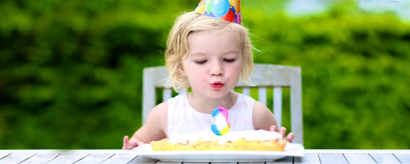 Wir feiern den dritten Geburtstag - Dreijähriges Kind vor einer Geburtstagstorte