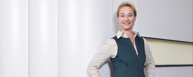 Grün als Hingucker - Frau in grünem Businesskostüm vor grauer Wand