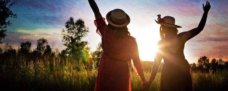 Der Weg zu mehr Mut und Selbstbewusstsein - Zwei Frauen Hand in Hand im Gegenlicht der Abendsonne