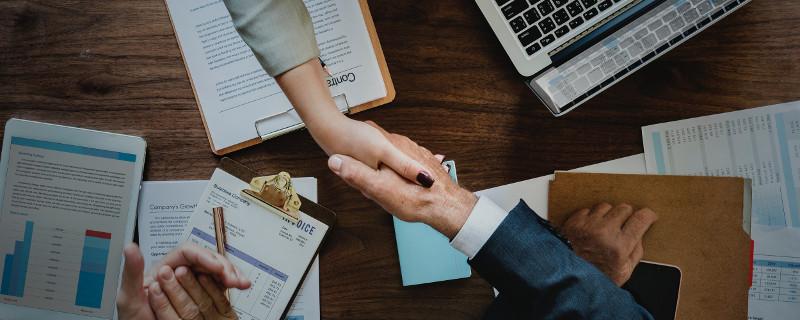 Tipps für Ihre Strategie und die Zusammenarbeit von Unternehmens-Recruitern und Personalberatern - Shake Hands über den Schreibtisch hinweg