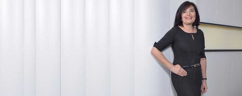 Schwarz unterschreicht Autorität und kann von allen getragen werden - Schwarz gekleidete Frau vor grauem Hintergrund
