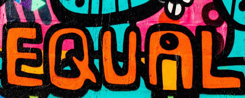 "Forderung nach Gleichheit - Graffito mit Schriftzug ""Equal"" an bunt bemalter Wand"