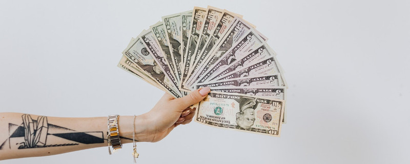 Tätowierte Hand mit Fächer von Dollarnoten