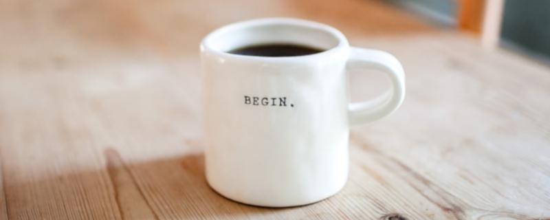 Kaffeetasse auf einem Holztisch, beschriftet mit dem englischen Wort Begin