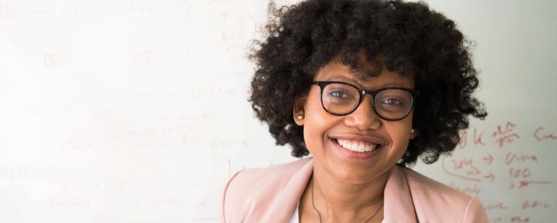 Junge Frau mit schwarzen Locken vor einem Whiteboard
