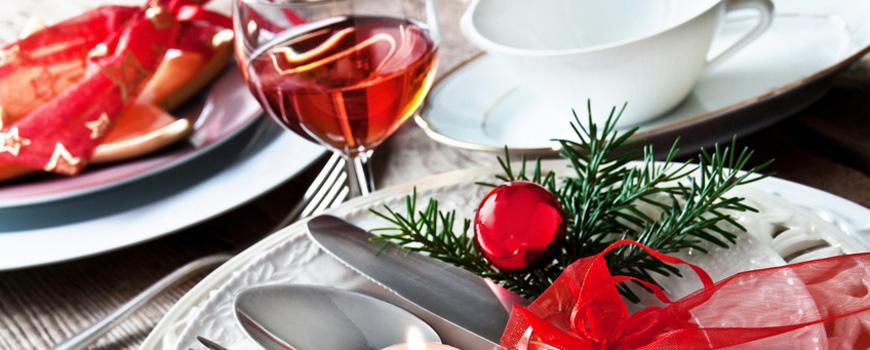 Weihnachtsgedeck mit Weinglas, Teetasse, Teller, Besteck und Tannenzweig