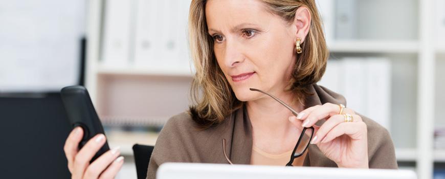 Frau betrachtet skeptisch das Display ihres Telefons