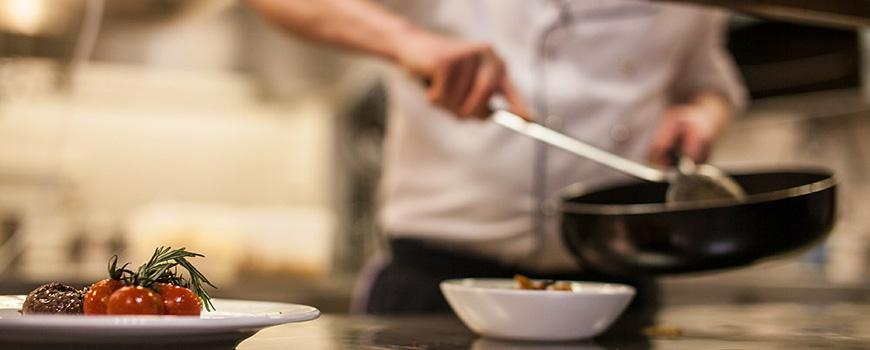 Bettina von Massenbach will die Gastrobranche retten - Koch mit Pfanne in der Küche verteilt Essen auf Teller