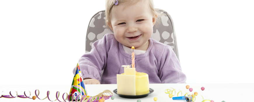 Kleinkind freut sich über erste Kerze auf dem Geburtstagskuchen