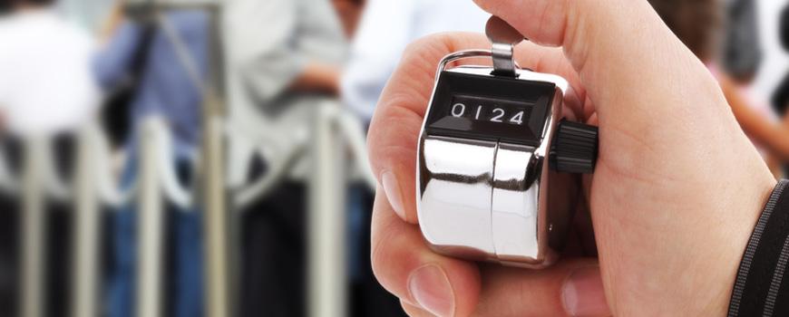 Hand mit Zähler zur Berechnung der Anzahl an vorbeigehenden Menschen
