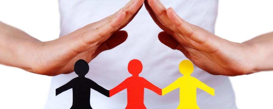 Schützende Hände über schwarz-rot-goldenen Papierfiguren