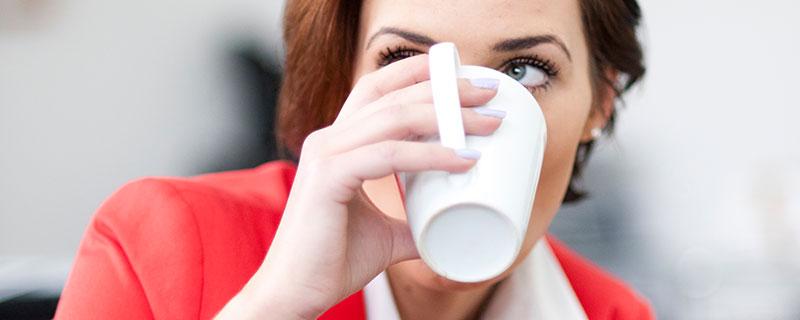 Foto - Frau mit Kaffeetasse am Mund, das Umfeld im Blick