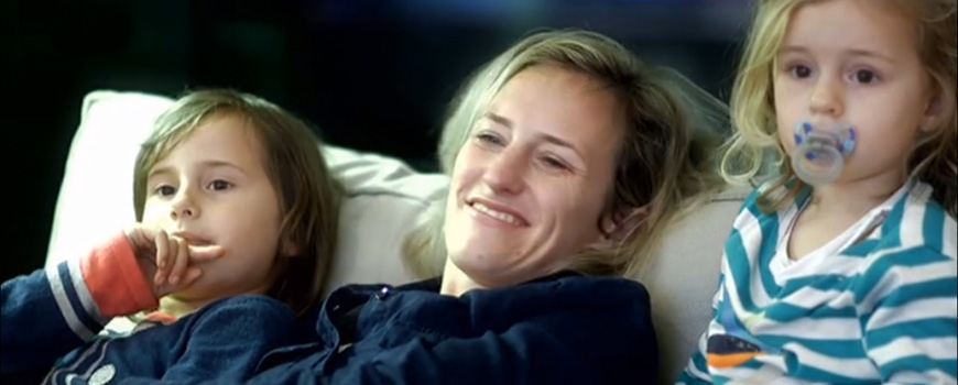 Mutter mit zwei Kindern genießt den Feierabend auf der Fernsehcouch