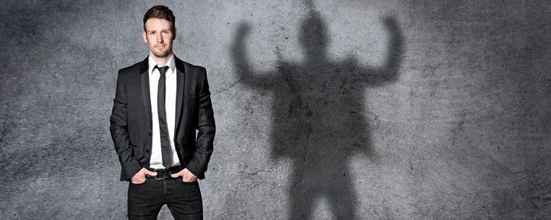 Innere Haltung und Macht - Gelassener Mann mit kraftstrotzendem Schatten an der Wand